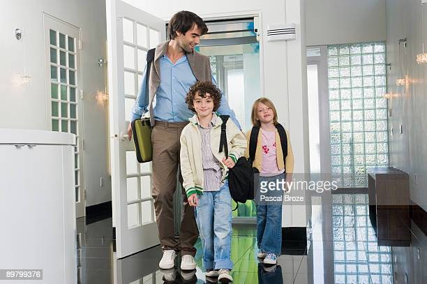 man with his children entering a house - ショルダーバッグ ストックフォトと画像