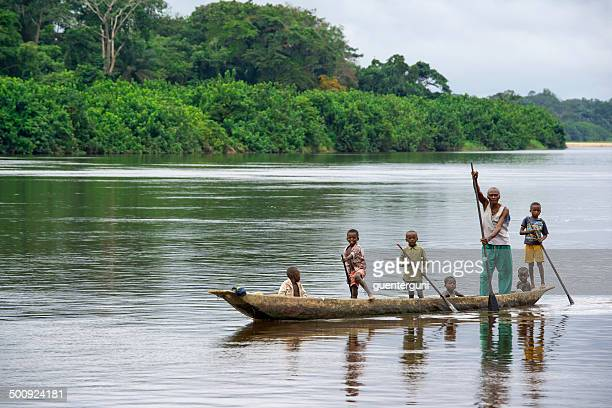 man with his children in a pirogue on congo river - dugout canoe stock photos and pictures