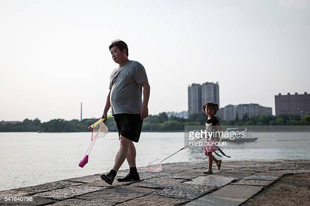A man with his daughter walk by Daming Lake in Jinan Shandong province on June 18 2016 Jinan is also called the 'Spring City' for its wellknown water...