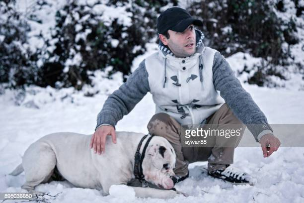 man with his dog in the snow - american bulldog stock photos and pictures