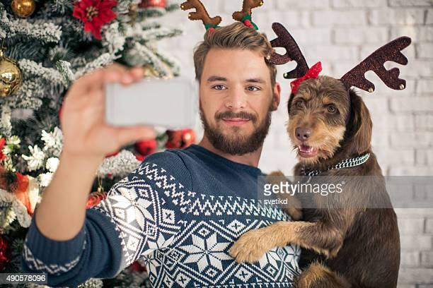 Mann mit seinem Hund nimmt selfies für Weihnachten.