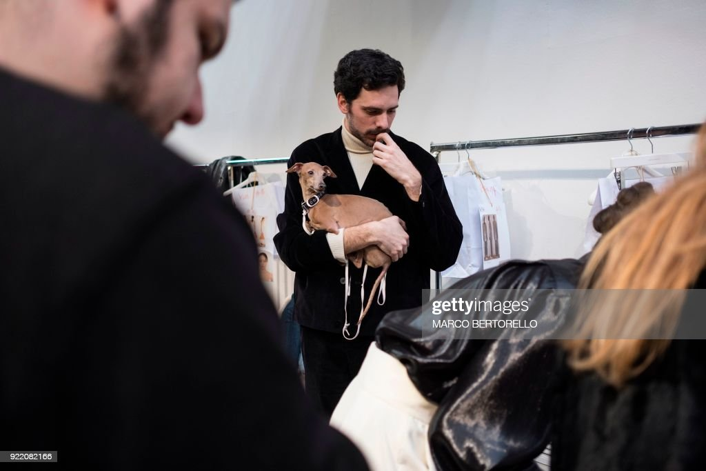 A man with his dog waits backstage prior to the women's Fall/Winter 2018/2019 collection fashion show by Lucio Vanotti in Milan, on February 21, 2018. / AFP PHOTO / Marco BERTORELLO