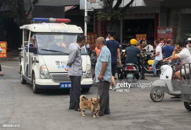 Man with his dog walks past a police cart during the Yulin dog meat festival at the Dashichang market in Yulin in China's southern Guangxi region on...