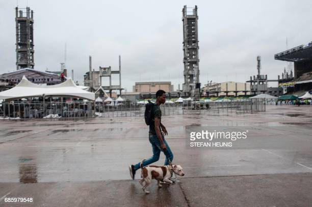 A man with his dog walks through the Tafawa Balewa Square at the Eyo Festival held in Lagos on May 20 2017 The whiteclad Eyo masquerades represent...