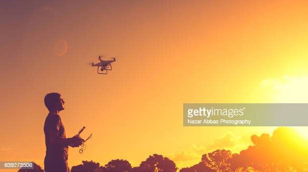 Man with his Drone and sunset in background.