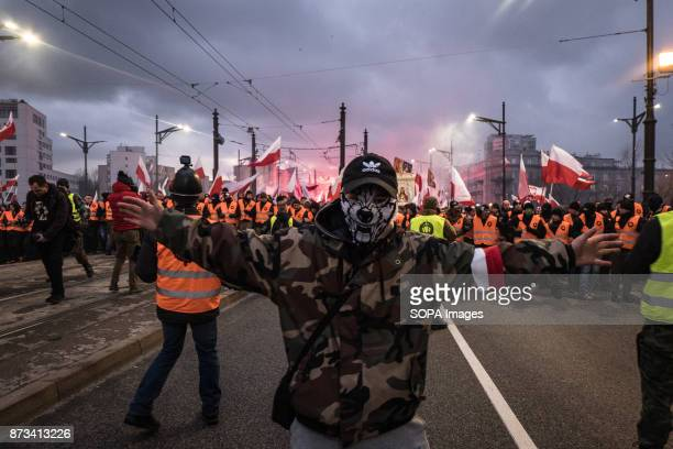 Man with his face covered as thousands gather for the annual nationalist march of Poland´s Independency Day Poland's Independence Day is a annual day...