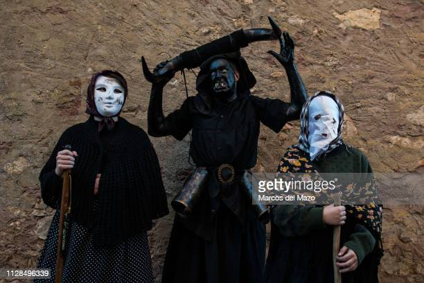 Man with his face covered in oil and soot and carrying bull horns representing a devil and women with masks posing during a traditional carnival...