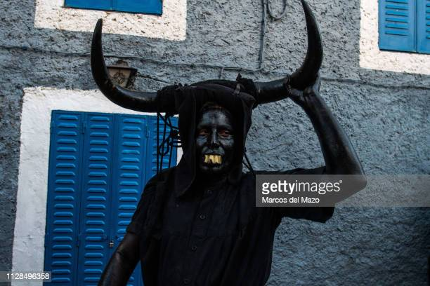 A man with his face covered in oil and soot and carrying bull horns representing a devil during a traditional carnival festival Every year Luzon...