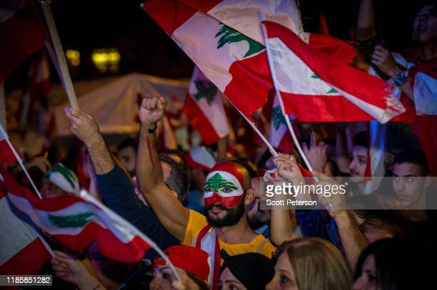 A man with his face painted like the national flag joins thousands of Lebanese protesters rally against sectarian government and call for the removal...
