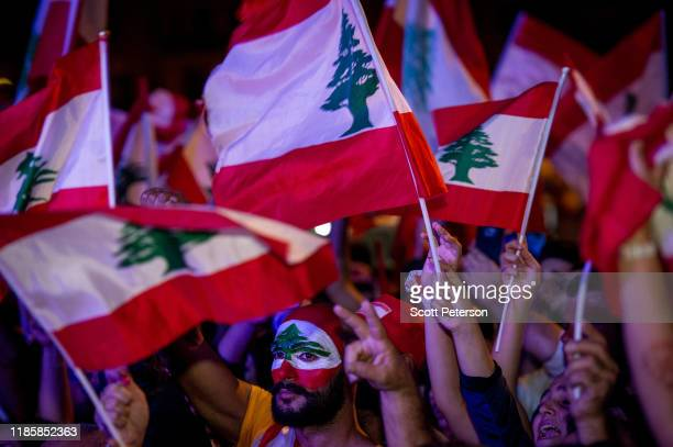 Man with his face painted like the national flag joins thousands of Lebanese protesters rally against sectarian government and call for the removal...