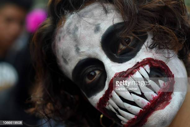 A man with his face painted takes part during a Zombie Walk organized to bring aid to the homeless on November 11 2018 in Mexico City Mexico