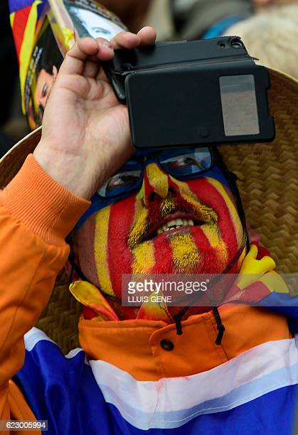 A man with his face painted with the 'Estelada' takes a selfie during a demonstration organized by ANC AMI and Omnium Cultural against Spains use of...
