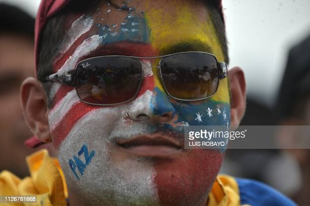 TOPSHOT A man with his face painted with the Venezuelan and US flags takes part in the Venezuela Aid Live concert organized by British billionaire...