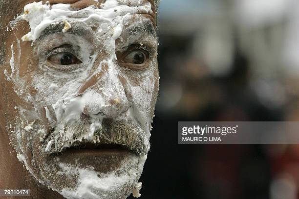 A man with his face smeared with icing gestures as he eats big slices of a 454meterlong cake made as part of the festivities for the 454th...