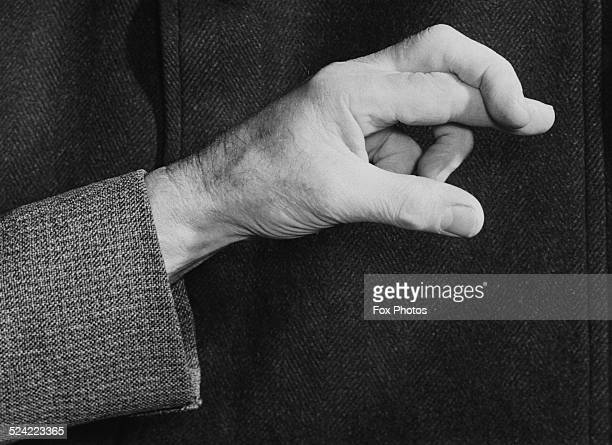 A man with his fingers crossed for good luck circa 1950