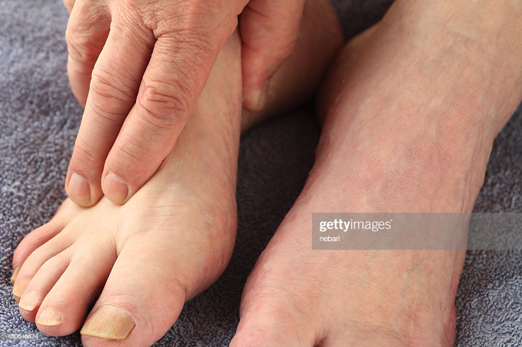 Man with his hand on a foot : Stock Photo