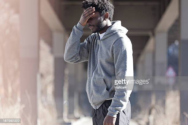 A man with his hand on his forehead with a look of dejection