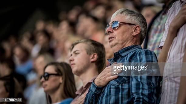 mann mit seiner hand auf sein herz während einer nationalhymne beim sport - geschworener stock-fotos und bilder