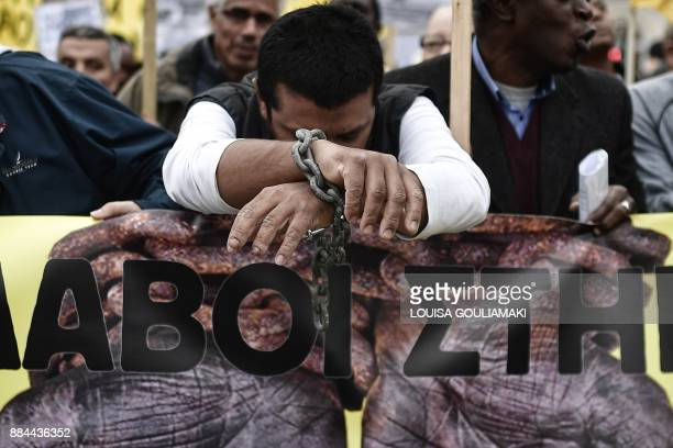 TOPSHOT A man with his hands chained takes part in a march towards the offices of the European Union during a demonstration on December 2 2017 in...