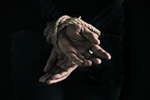 man with his hands tied behind his back