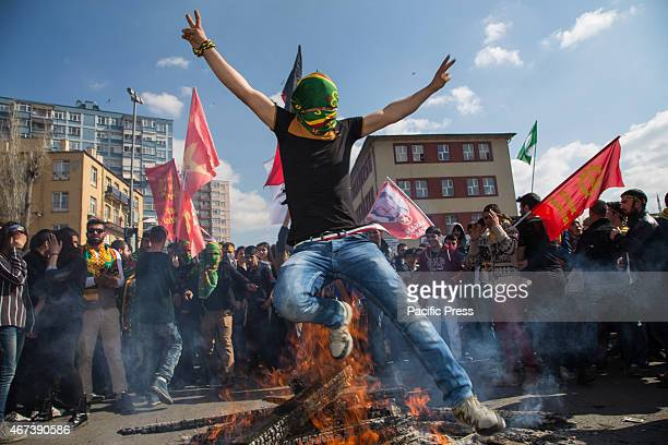 Man with his head covered by a Kurdish flag jumps over the fire at the Newroz celebration rally. Newroz is a spring festival marking the beginning of...