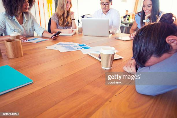 Man with his head down in a meeting.