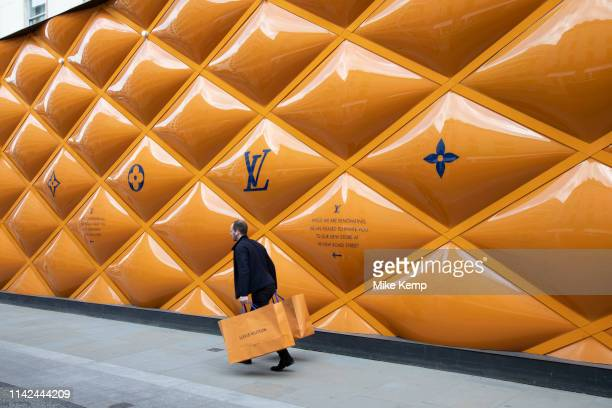 Man with his matching shopping bags passes the yellow temporary hoarding covering exclusive clothes shop window Louis Vuitton on New Bond Street in...