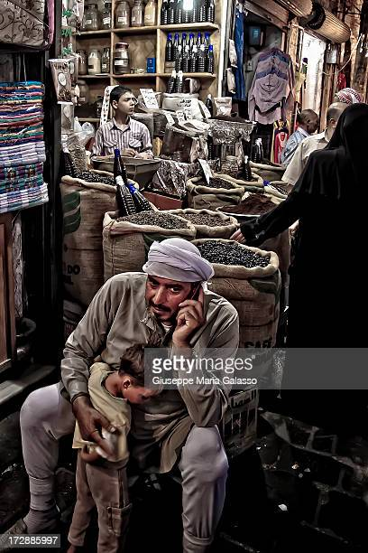Man with his mobile phone while embracing his son at Aleppo's souq.