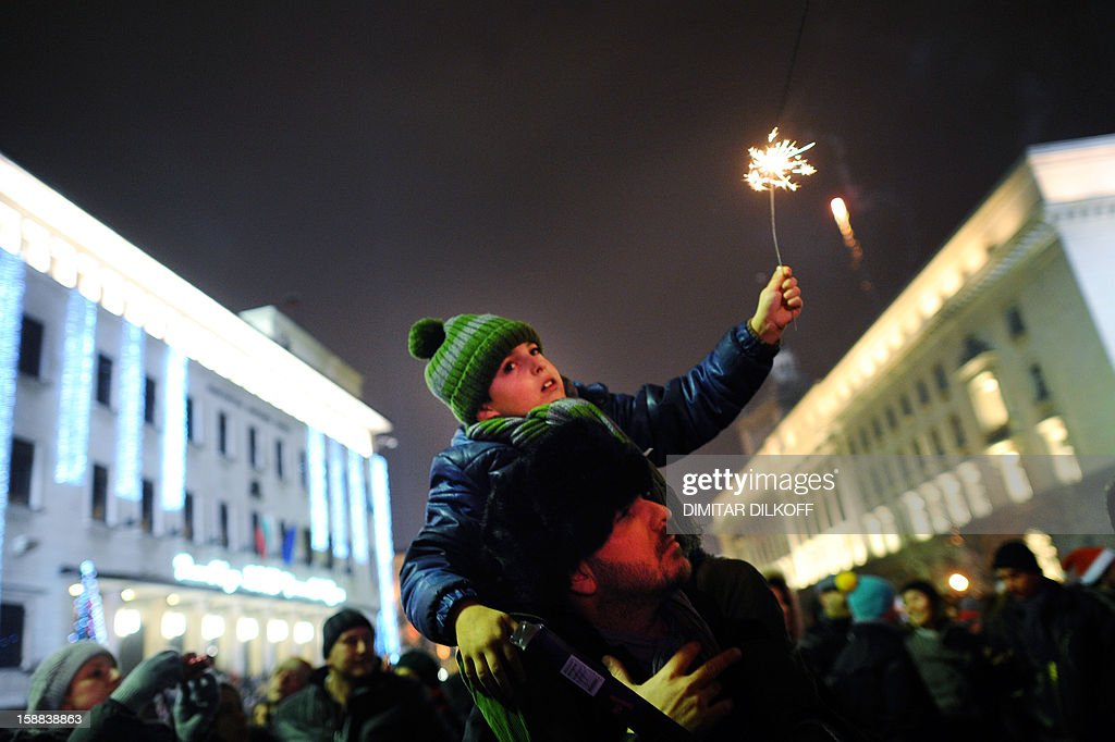 A man with his son celebrates the New Year at Sofia's Alexander Batemberg Square, early January 1, 2013.