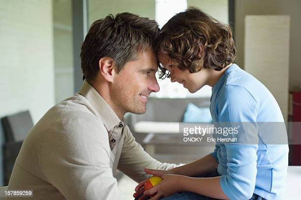 man with his son face to face and smiling - onoky stock-fotos und bilder