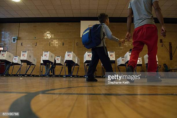 A man with his son walk past voting booths at Public School 22 on April 19 2016 in the Brooklyn borough of New York City Voters are going to the...