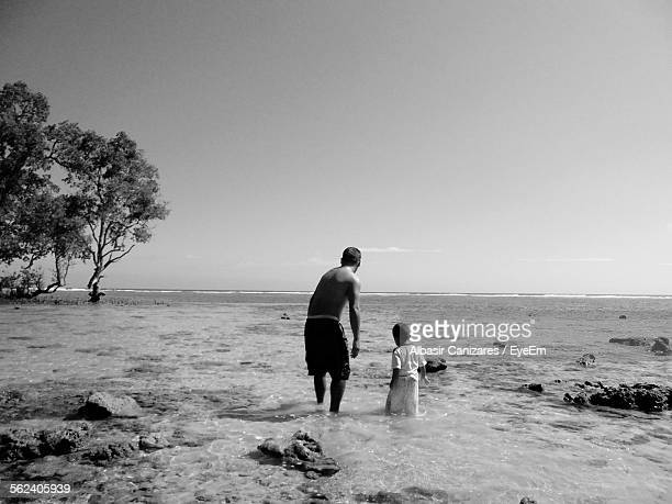 Man With His Son Walking On Beach