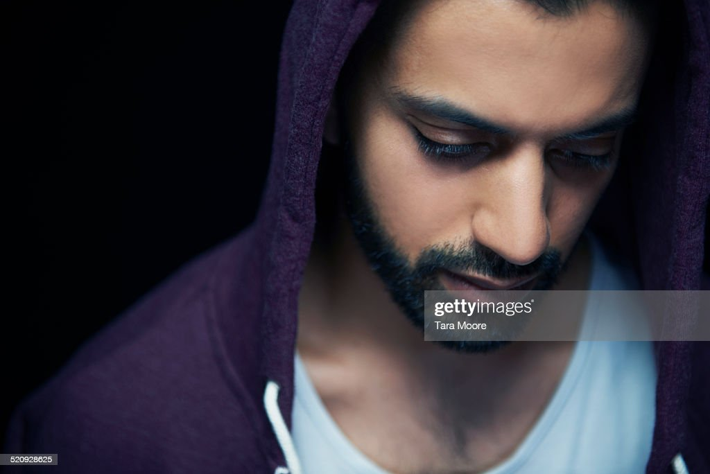 man with hoodie looking down : Stock Photo