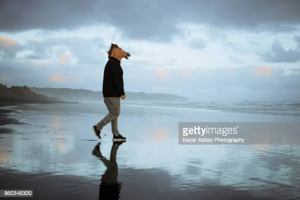 Man with horse head walking on beach.