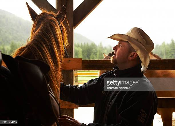 man with horse in barn - one man only stock pictures, royalty-free photos & images