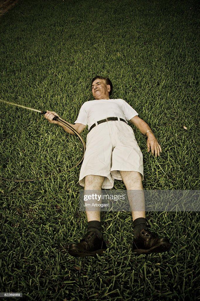 Man with hose lying on ground : Stock Photo