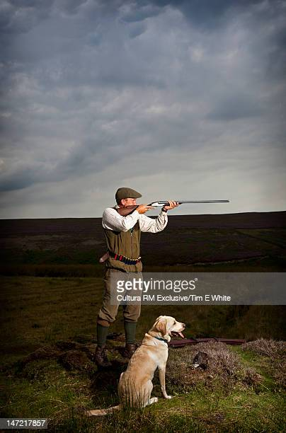 Man with hunting rifle and dog