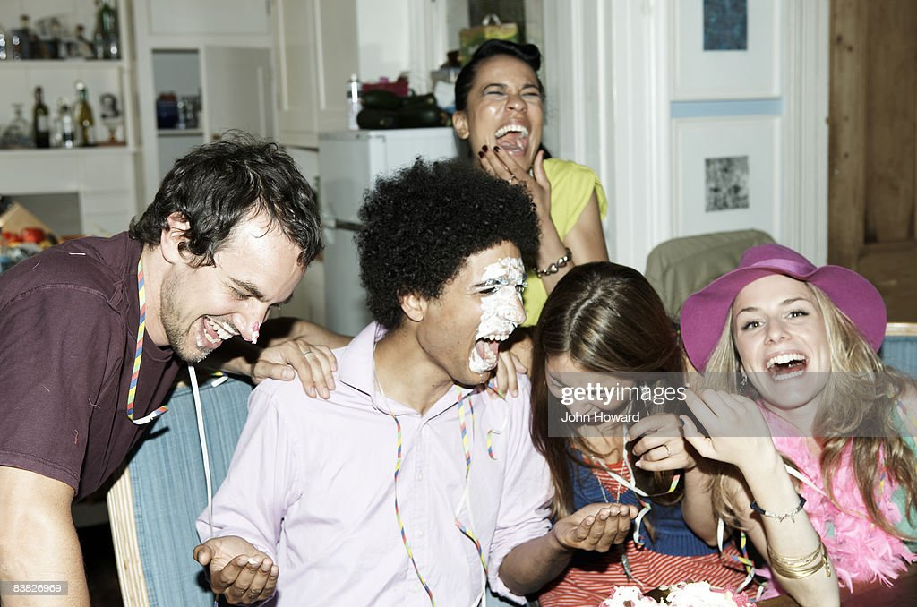Man with icing on his face laughing with friends : Stock Photo