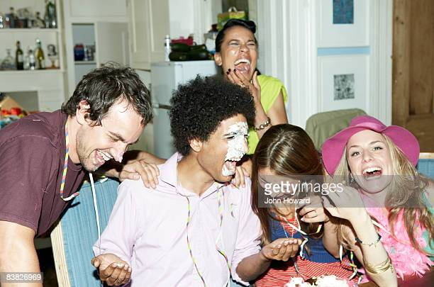 Man with icing on his face laughing with friends