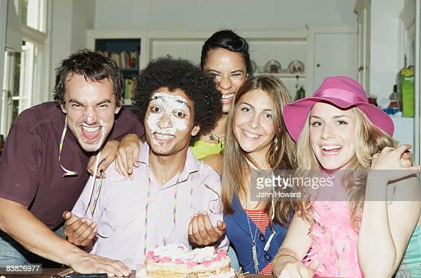 Mann mit Zuckerguss auf seinem Gesicht, posieren mit Freunden