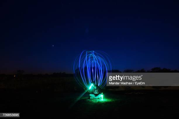 Man With Illuminated Glow Stick Performing Light Painting On Field Against Sky At Dusk
