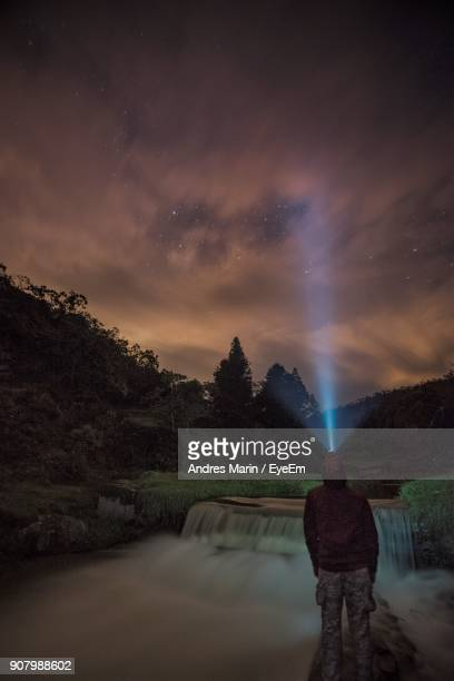 Man With Illuminated Headlamp Standing By River Against Star Field