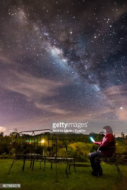 Man With Illuminated Lighting Equipment While Sitting On Field Against Milky Way