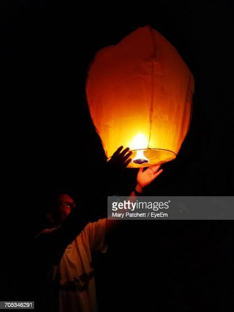 man with illuminated paper lantern at night - lantern festival stock photos and pictures