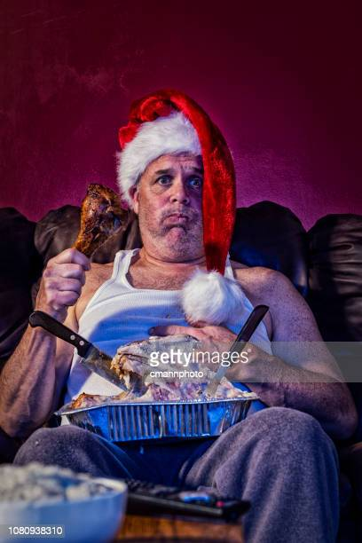 a man with indigestion from a leftover turkey dinner with carcass in his lap holding a drumstick wearing a santa hat - funny turkey images stock photos and pictures