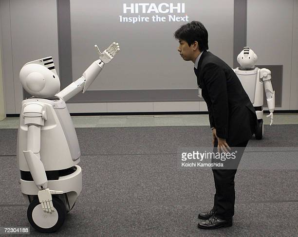 A man with Japanese electronics conglomerate Hitachi's New Humaniod Robot 'Emiew' impressed with their chat and fast moves during a demonstration on...