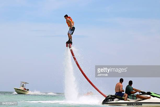 Man with jet pack in air Flyboarding with safety handlers