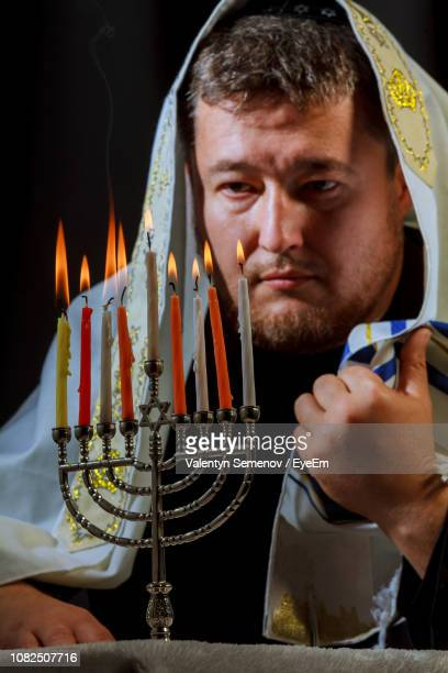 Man With Jewish Prayer Shawl Looking At Menorah