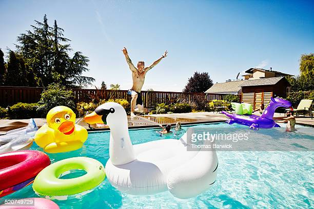 man with jumping into pool during party - pool party stock pictures, royalty-free photos & images