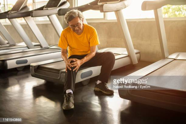 man with knee pain sitting on treadmill in gym - down on one knee stock pictures, royalty-free photos & images